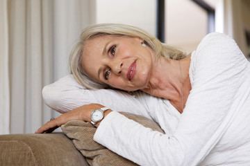 Close up relaxing older woman sitting on sofa at home