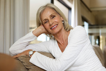 Close up smiling older lady relaxing on sofa at home
