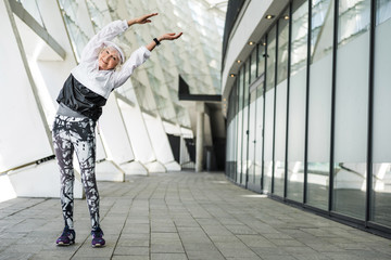 Joyful elderly lady warming up by modern city building