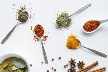 Top view of various dried aromatic spices in metal and ceramic spoons