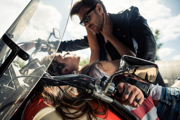 Beautiful stylish young couple in love spending time together on motorcycle