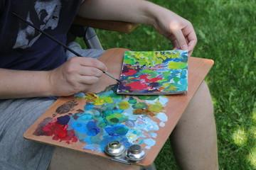 Künstler malt ein Bild von einer Sommerwiese