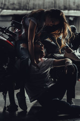 Sensual young woman sitting on motorbike and hugging young man sitting on pavement