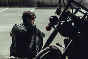 Back view of stylish young man in leather jacket sitting near motorbike and looking away Wall mural