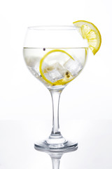 Glass of gin tonic with lemon on white background
