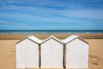 Three traditional white wooden beach huts on the beach of Villers, Normandy, France