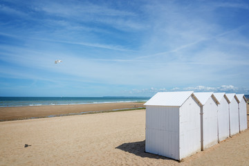 Traditional white wooden beach cabins on the beach of Villers, Normandy, France