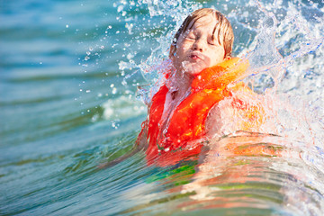Little boy in orange life vest swimming in wave sea (selective DOF)