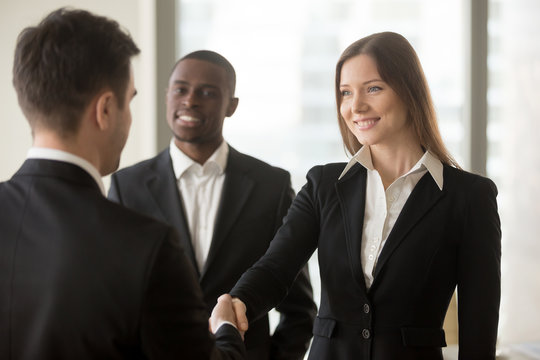 Beautiful smiling businesswoman and businessman handshaking standing in office, nice to meet you, first impression, being promoted rewarded for good work, employee of the month, career development