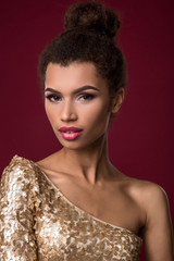 Fashion young African woman with make-up, in sexy gold dress.