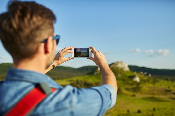 Hiking man taking photo with smart phone