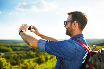 Man hiking with backpack taking photo with his mobile phone outdoors
