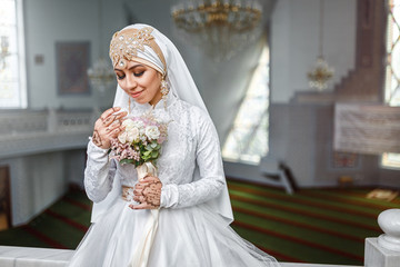 Muslim bride with jewelery in a headscarf hijab with a bouquet of flowers in a mosque