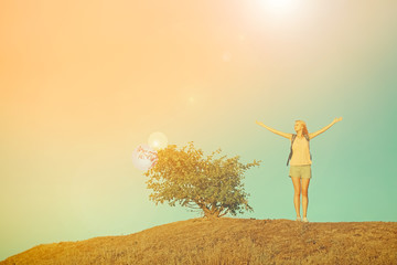 Young woman on hill on blue sky background