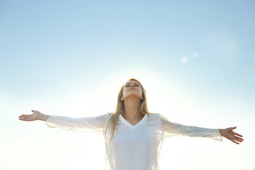 Happy young woman on sky background