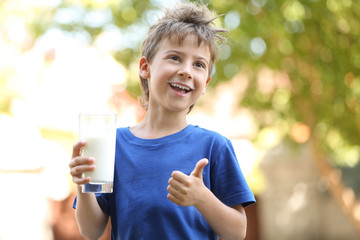 Cute boy in blue shirt holding glass of milk on blurred background