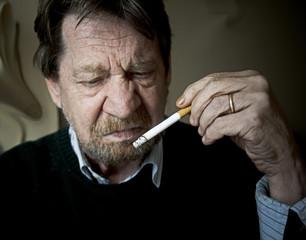 Uomo anziano, smorfia di disgusto per la sigaretta.