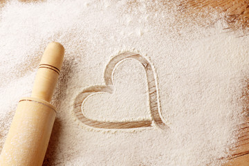 Heart drawn on flour and rolling pin on wooden background