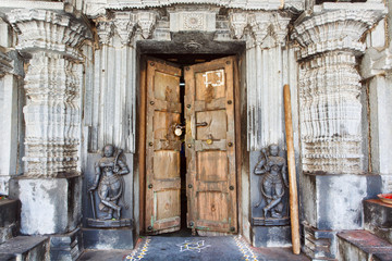 Wooden door in historical Hindu temple with stone walls, collumns, carvings and sculptures, India.