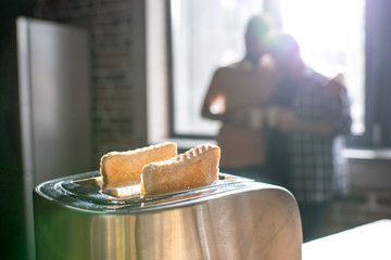 Close-up view of shiny metallic toaster with fresh crunchy toasts indoors