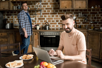 Smiling bearded man sitting at table and using laptop while partner pouring coffee behind