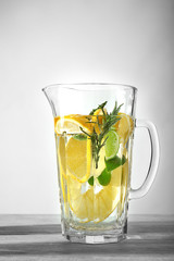 Jug with fresh lemonade on table