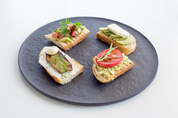 Variety of toast with vegetables as avocado, tomato, eggplant, cucumber, garlic and cheese