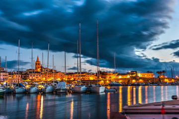 Overcast sky over Alghero harbor at night