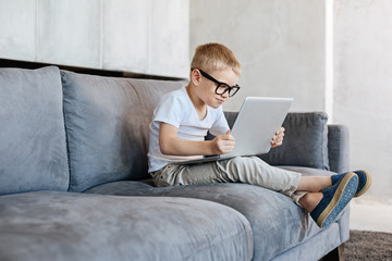 Attentive savvy kid reading something in the internet