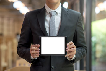 Young Businessman in black suit showing empty white tablet screen, business project presentation with digital device, technology for smart working concepts