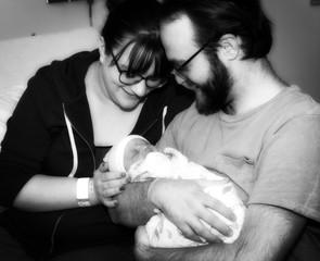 New Mother & Father Hold Their Newborn Daughter at the Hospital