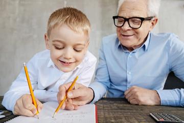 Enthusiastic nice man teaching his grandchild math