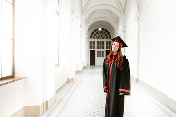 Beautiful, happy, fun, girl graduate in the mantle standing in the hallway of the university and smiles, study concept, space for text