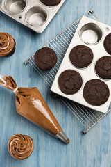 Decorating Chocolate Cupcakes with Frosting in Pastry Bag