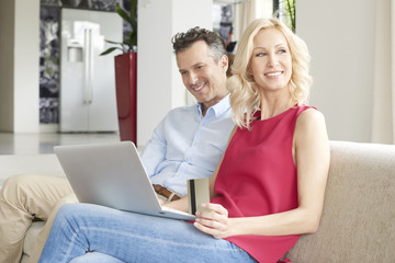 Spending money on the internet. Shot of a happy middle aged couple using laptop and credit card while sitting at home and shopping online.