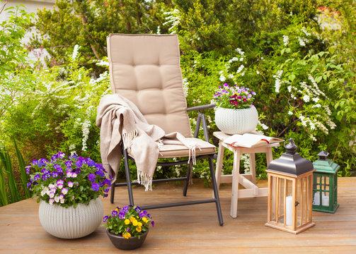 garden chair and table on terrace flowers  bush
