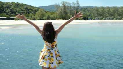 woman of freedom in the sea by outstretched two arm with sunlight