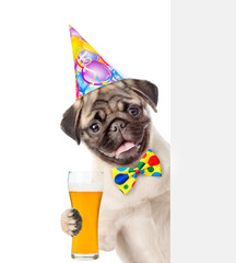 Happy Dog in birthday hat with tie bow holding light beer and peeking above white banner. isolated on white background
