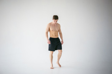 portrait young sexy handsome man of strong Athlete's body with bare torso, Dressed in a black sports shorts, Posing on white studio background