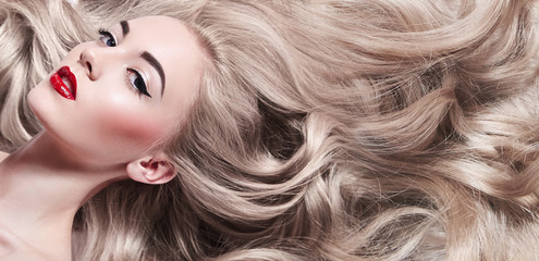 Beautiful young well-groomed girl lies - close-up. Long light shiny healthy well-groomed long hair. Advertising of hair care, cosmetics, beauty. Makeup - red lips, black arrows, mascara.