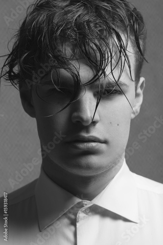Male beauty concept. Portrait of young man with perfect haircut wearing white classic shirt. Old Hollywood star style. Wet curly hair. Close up.