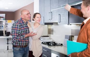 Couple examines kitchen cabinets