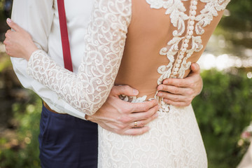 White bridal couple. Happy beautiful bride and handsome groom embraces in park outside. Closeup of luxury lacy back of white dress of young woman and male hands on her waist. Horizontal color picture.