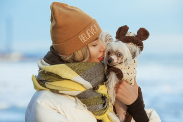Winter vacation concept. Couple of friends standing on beach near water with ice. Blond girl kissing her Chinese crested dog. Hipster style. Sunny weather. Happy together. Close up. Outdoor shot