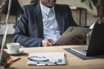 Businessman sitting at desk and reading files