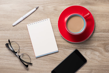 Blank white notebook open, eyeglass, pen and cup of coffee on the desk