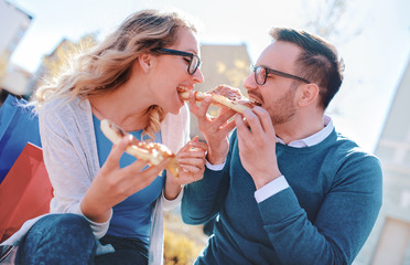 Couple eating pizza outdoors. Dating, consumerism, food, lifestyle concept