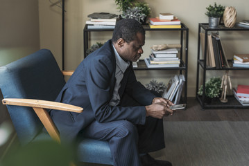 Middle-aged African businessman sitting on armchair and typing on cell phone.