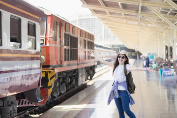 Portrait cute asian traveler sit at train station. Feeling funny and happy. Travel summer concept