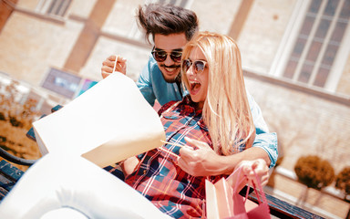 Shopping surprise. Young couple in shopping. Consumerism, love, dating, lifestyle concept